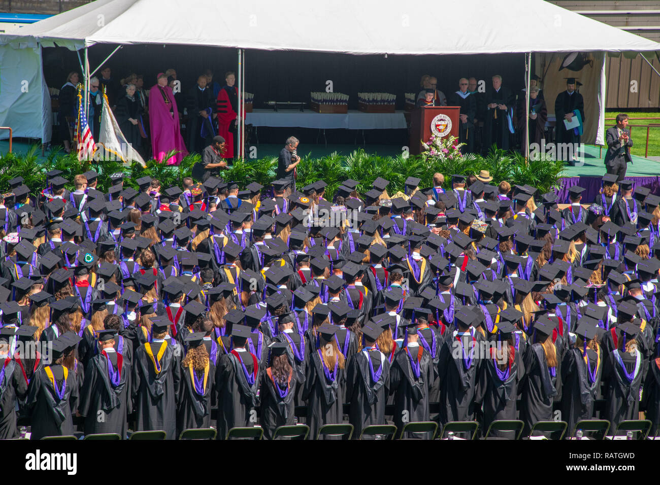 Worcester, Massachusetts--May 22, 2015. Graduating seniors stand wearing caps and gowns at the Holy Cross commencement ceremony. - Stock Image