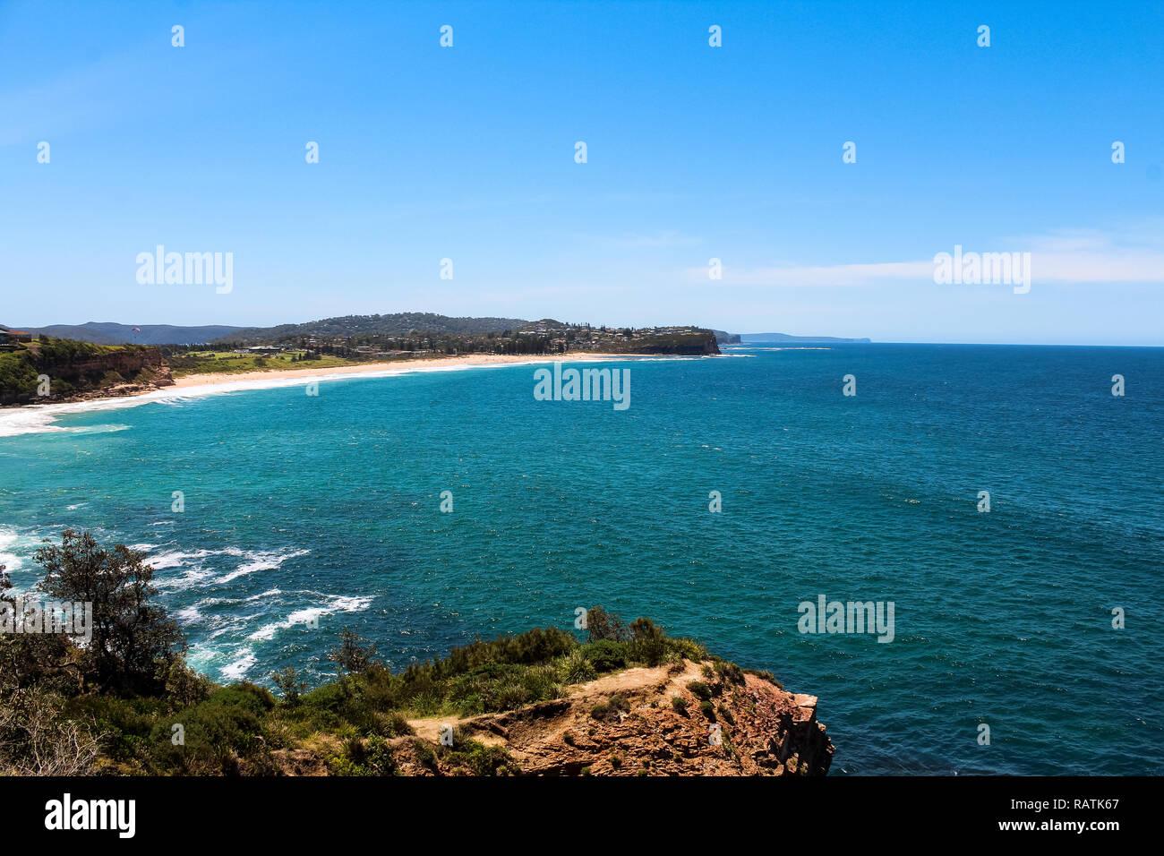 Turimetta Head Viewpoint looking towards Mona Vale Beach, one of Sydney's Northern beaches on a cloud-free summer day (Sydney, Australia) - Stock Image
