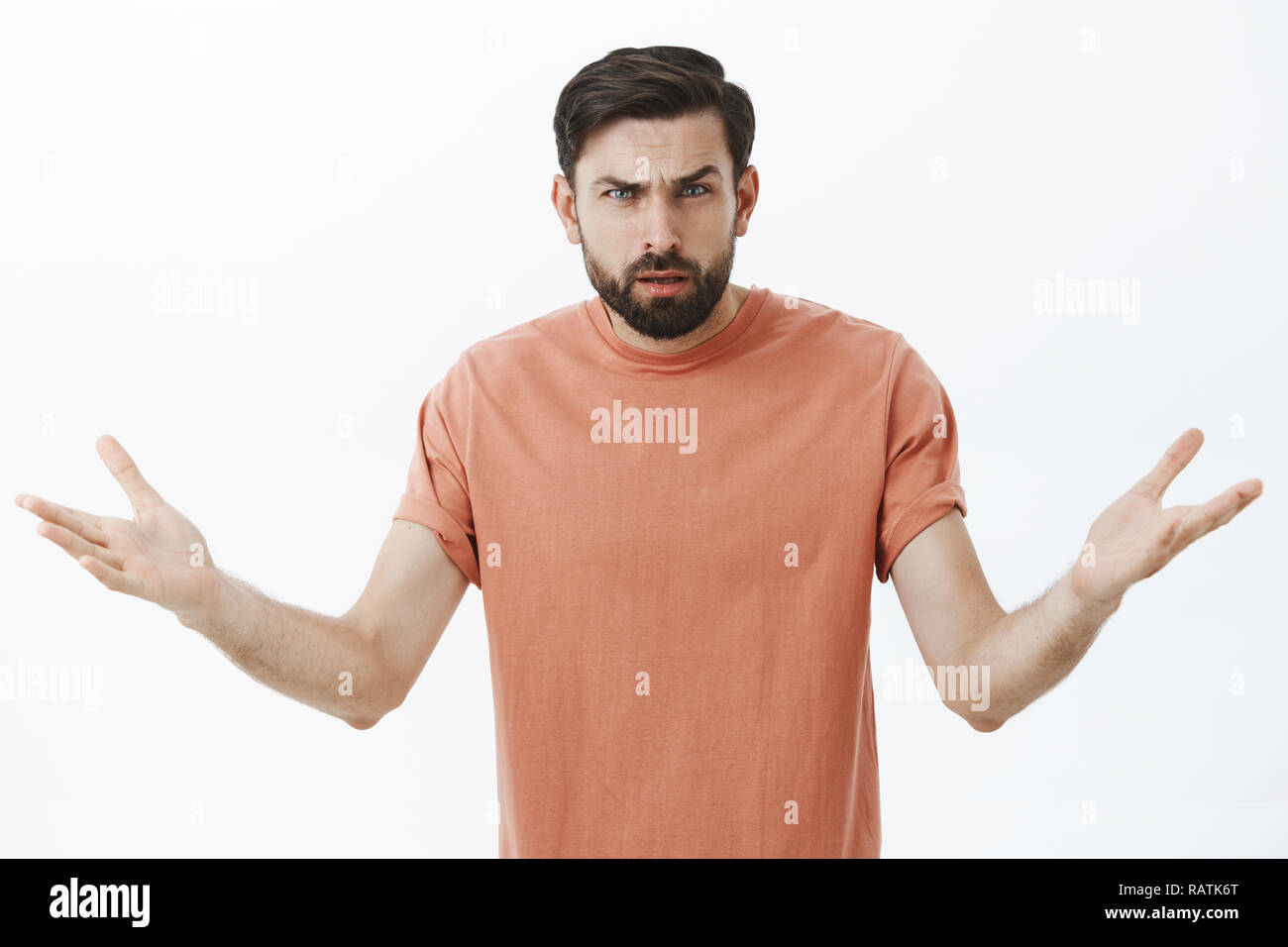 Confused and annoyed angry bearded boyfriend cannot understand why arguing, frowning with clueless emotions shrugging raising hands sideways in dismay, asking question intense and irritated - Stock Image