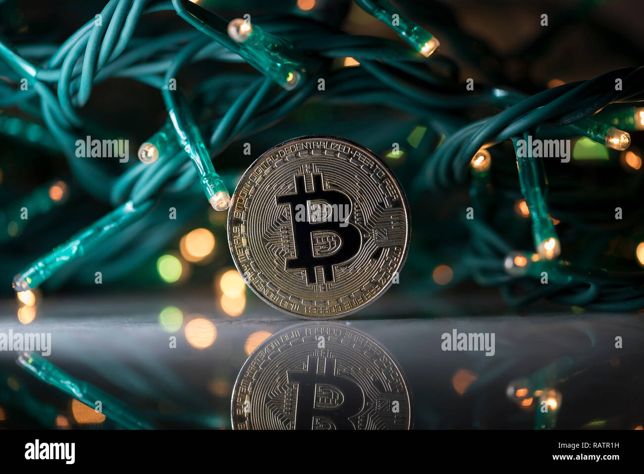 Bitcoin cryptocurrency physical coin placed next to Christmas lights - Stock Image