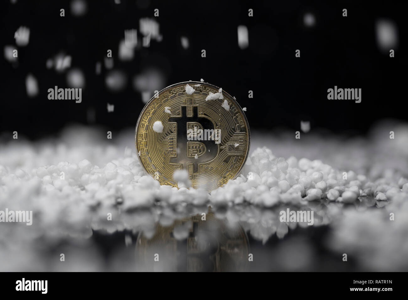 Bitcoin cryptocurrency physical coin surrounded and poured on with the fake snow in the black background - Stock Image