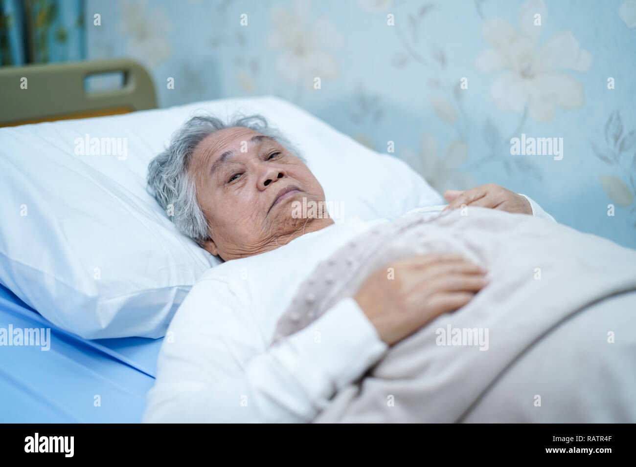 Asian senior or elderly old lady woman patient smile bright face with strong health while lying on bed in nursing hospital ward : healthy medicine. Stock Photo