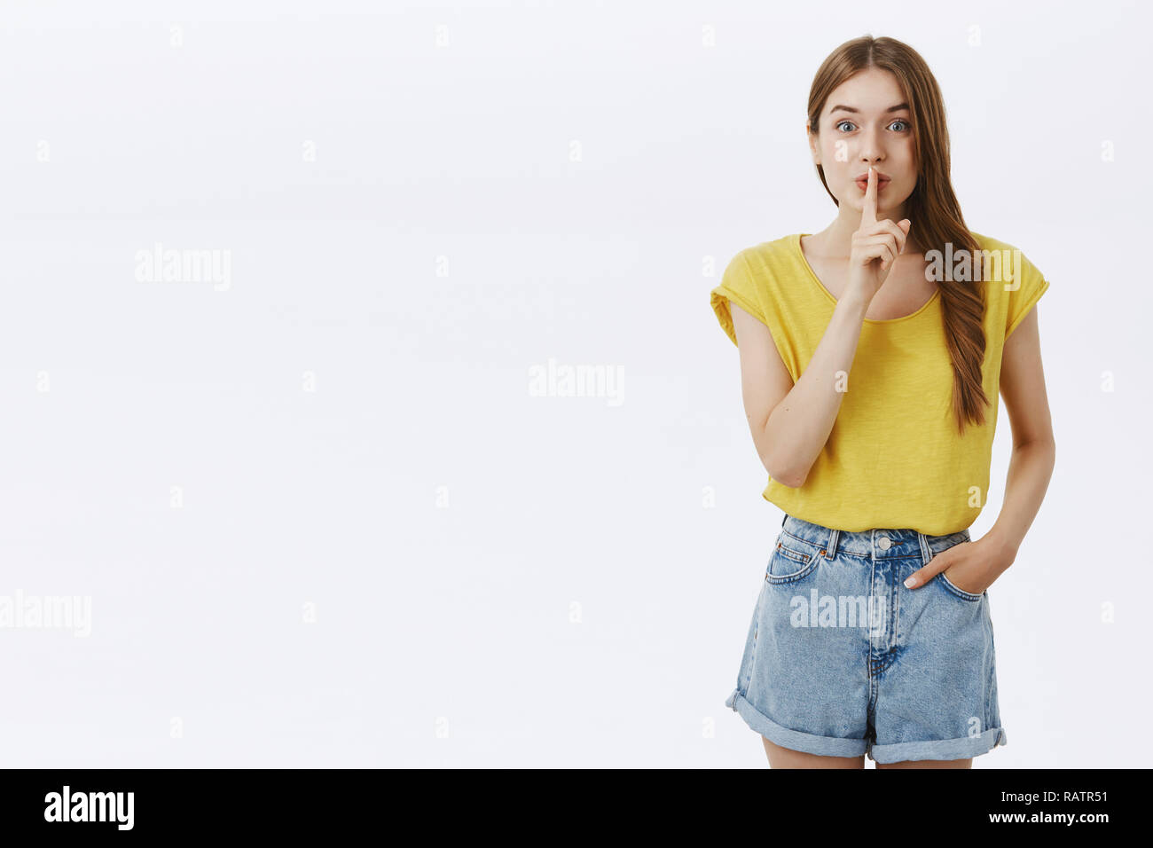 Shh please keep secret. Charming enthusiastic adult pretty woman with cute hairstyle folding lips gazing excited at camera showing shush gesture with index finger over mouth making surprise - Stock Image