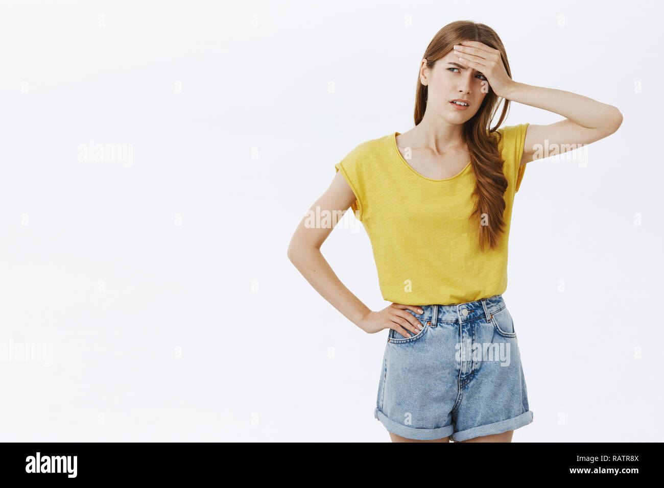 Give me break. Portrait of tensed displeased and bothered good-looking female in yellow t-shirt and shorts holding hand on forehead frowning looking tired left with dissatisfaction - Stock Image