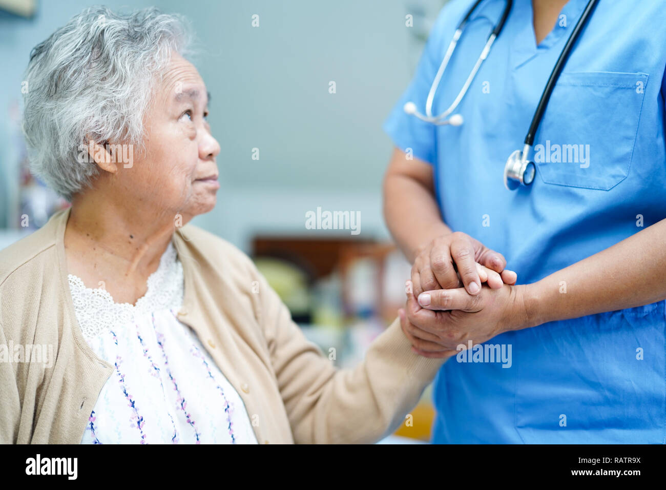 Holding Touching hands Asian senior or elderly old lady woman patient with love, care, helping, encourage and empathy at nursing hospital ward. Stock Photo