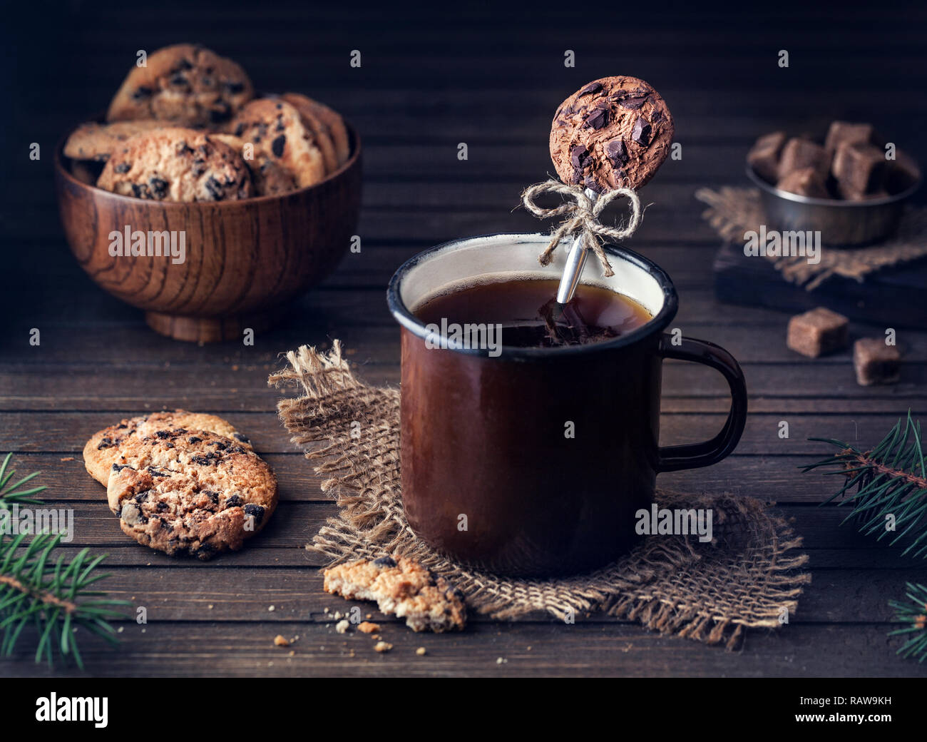 Decorative spoon from polymer clay in the mug with tea near chocolate cookies on wooden background - Stock Image