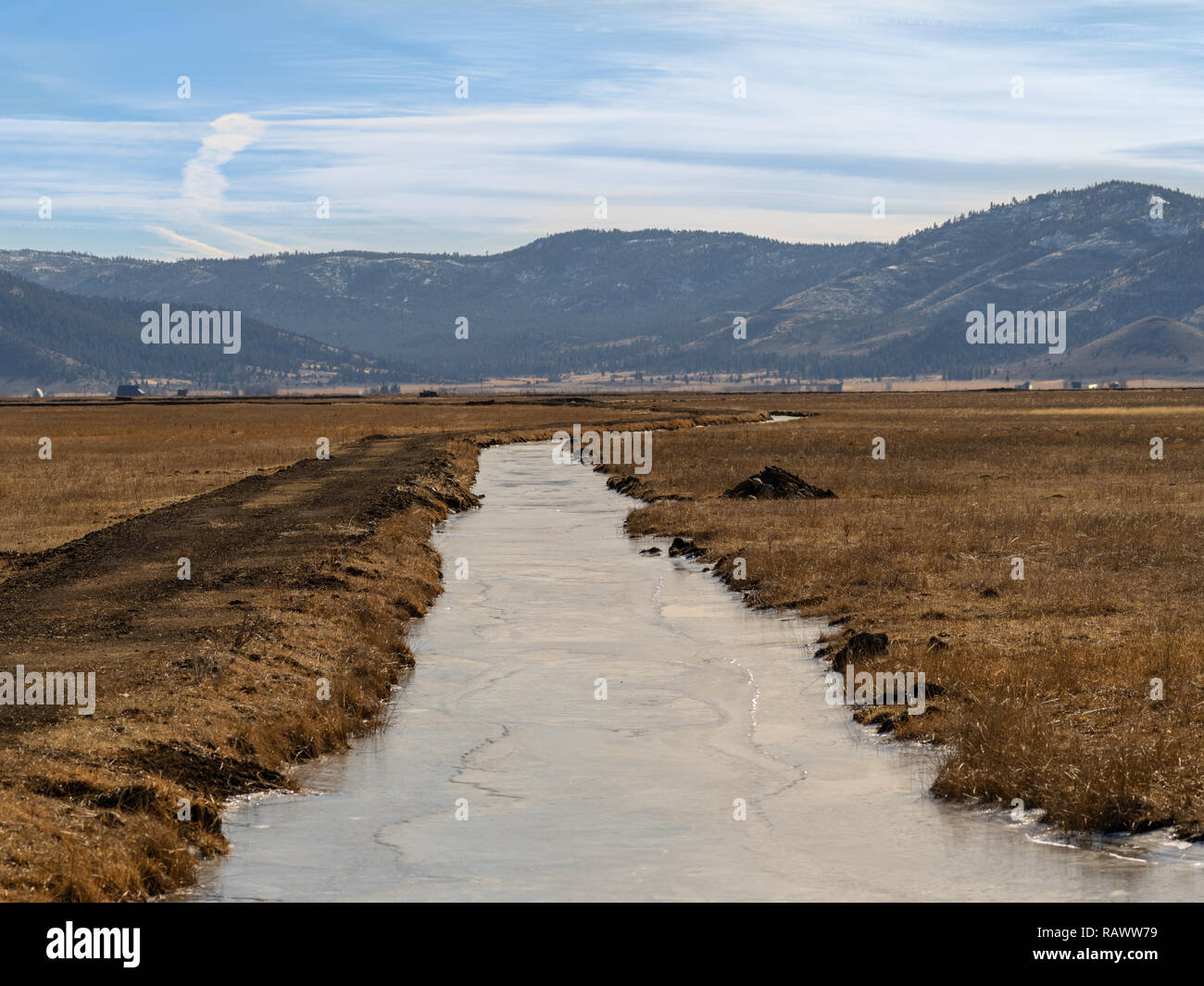Frozen Irrigation ditch or canal leading away towards some distant mountains. - Stock Image
