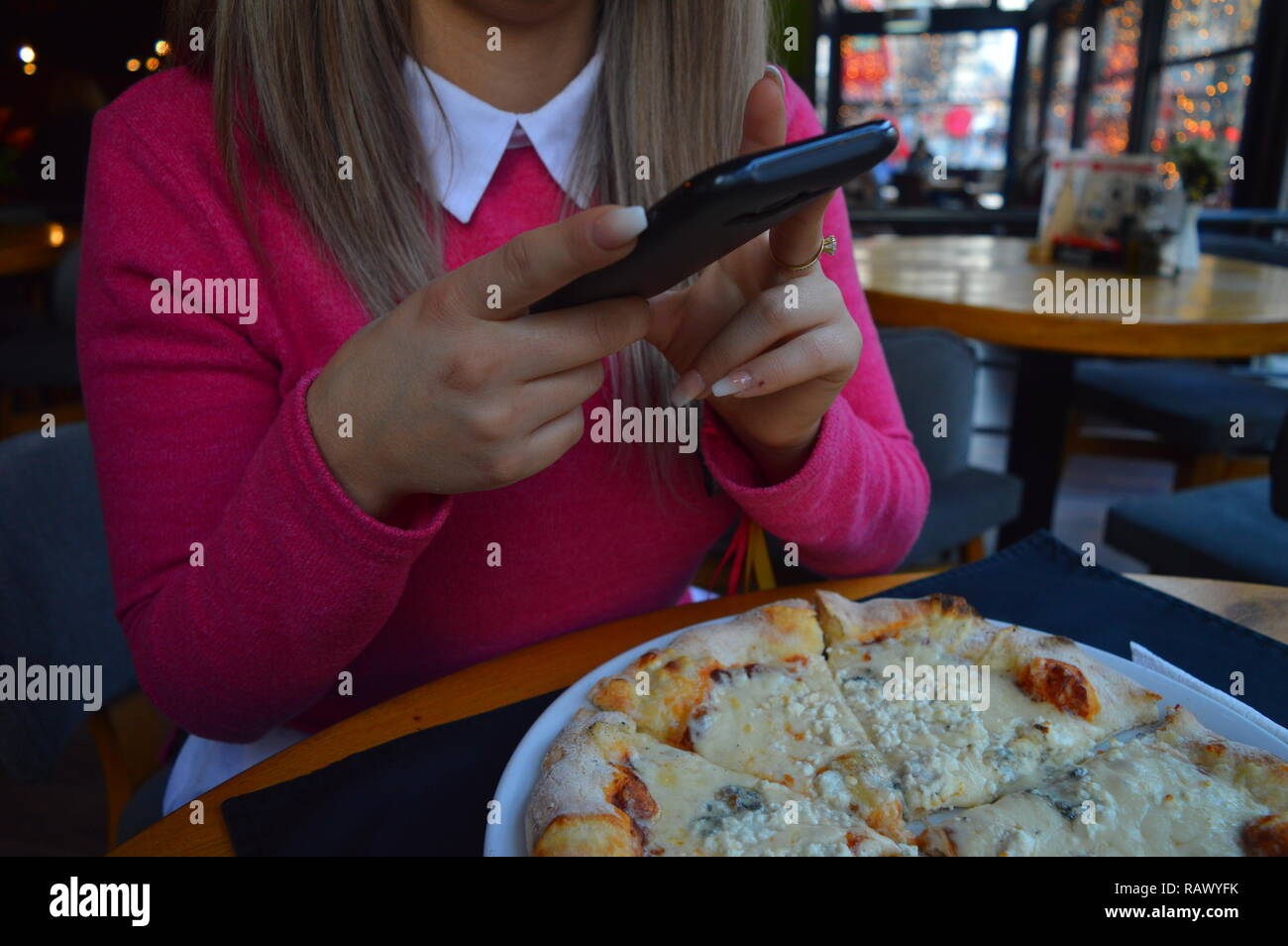 Girl photographing her pizza at a restaurant - Stock Image