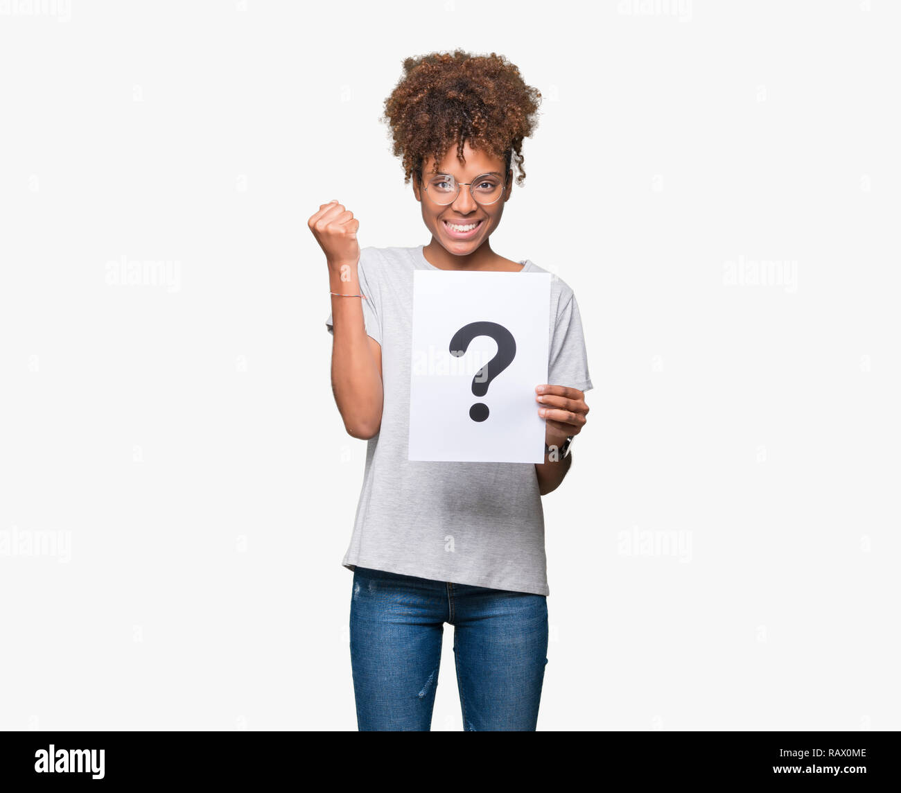 Young african american woman holding paper with question mark over isolated background screaming proud and celebrating victory and success very excite - Stock Image