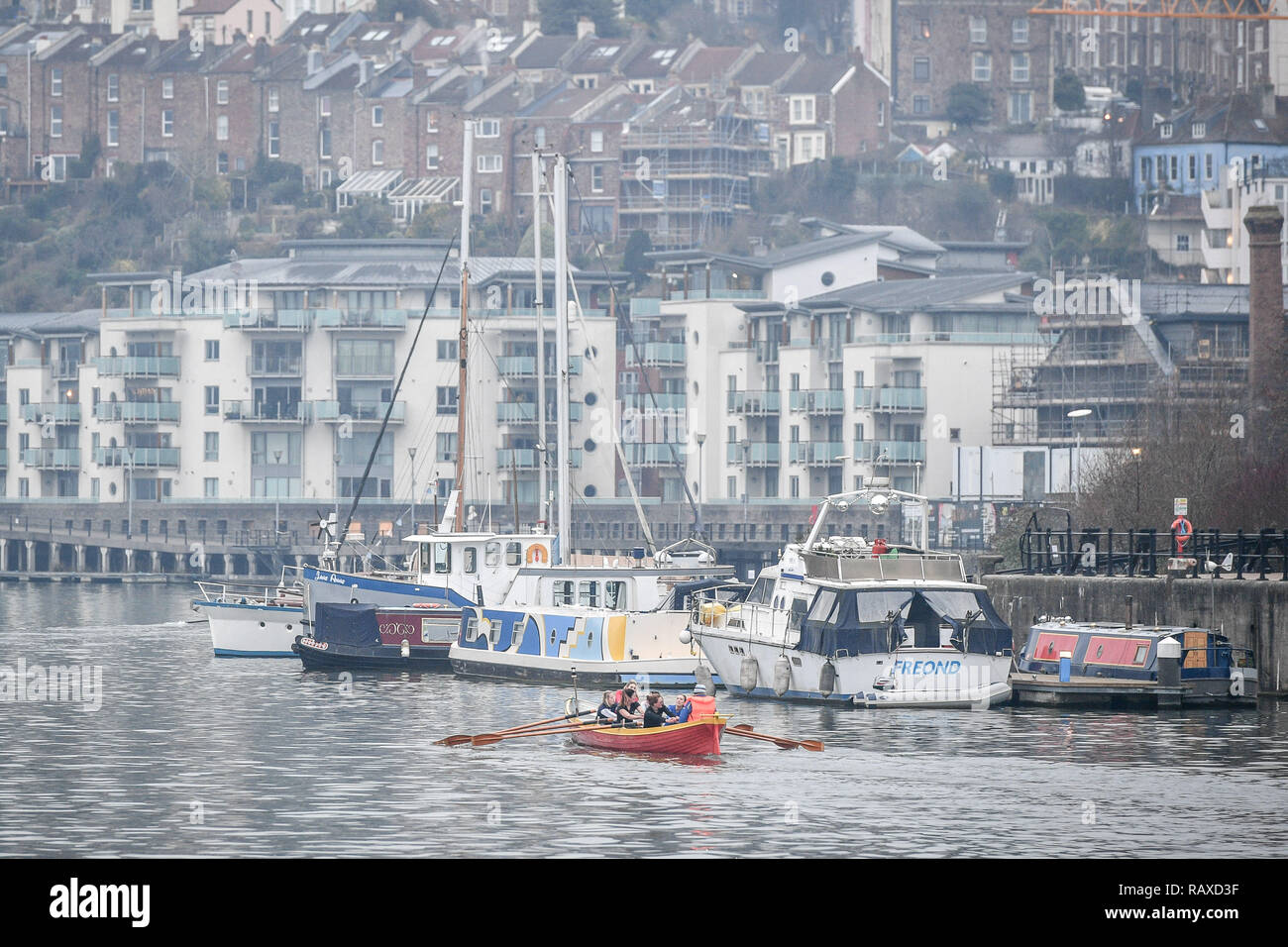 Rowers glide past boats moored on the Harbourside in Bristol, as temperatures drop across the UK. - Stock Image