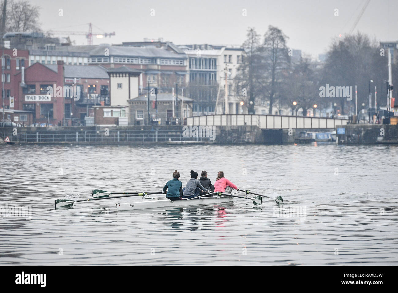 Rowers glide across the Harbourside in Bristol, as temperatures drop across the UK. - Stock Image