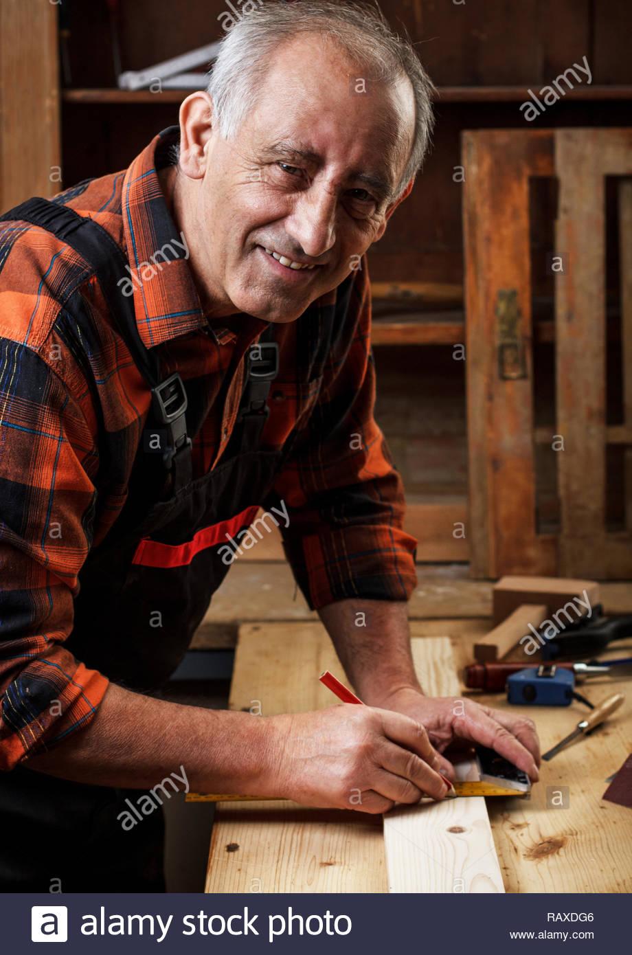 Senior carpenter working in his workshop, restoring the old furniture. - Stock Image