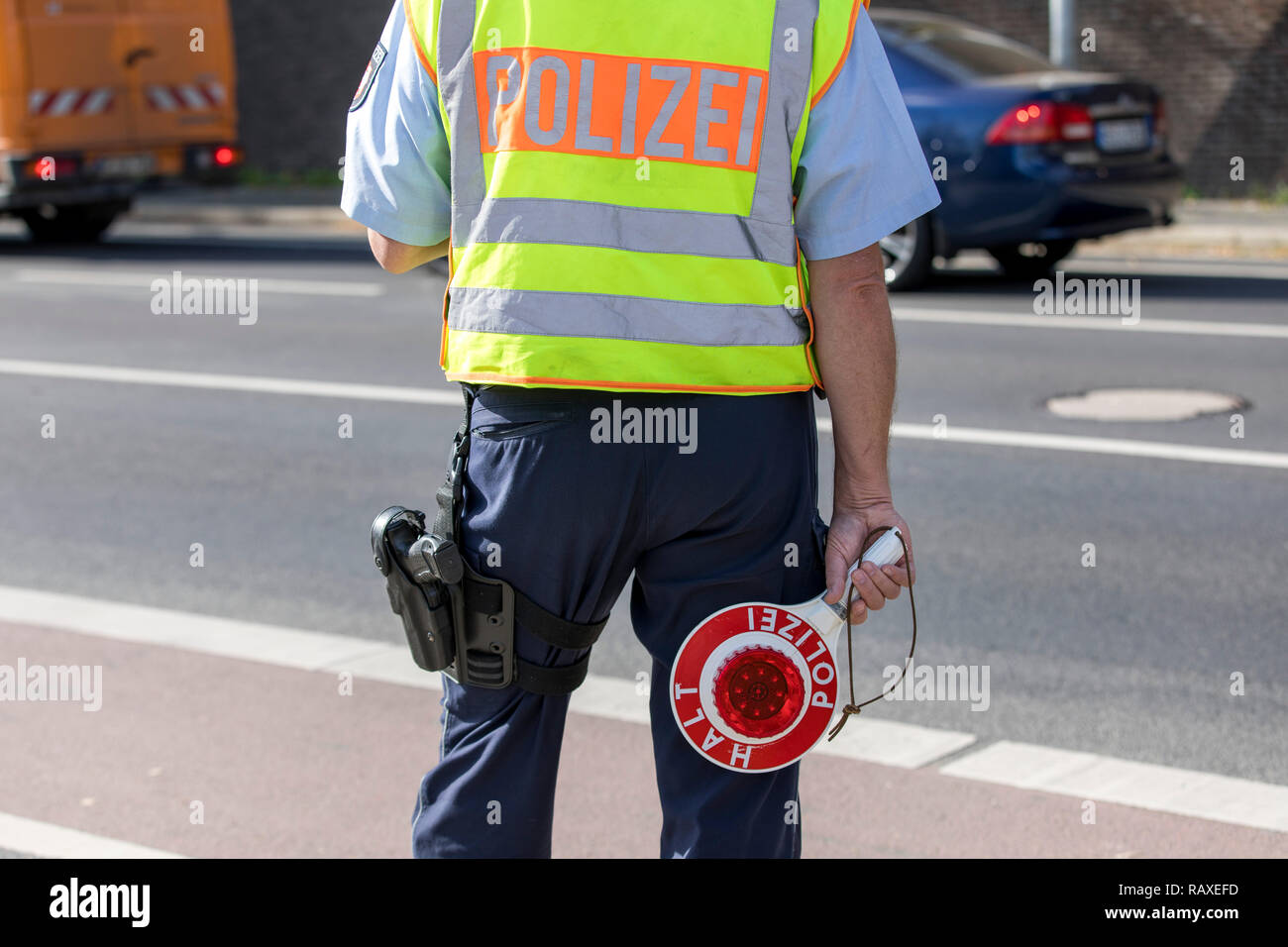 Policeman with yellow safety vest and stopping trowel, during a traffic control, Germany, Stock Photo
