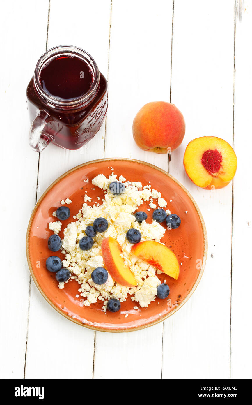 Still life with curd, blueberry and peach on a white wooden background - Stock Image