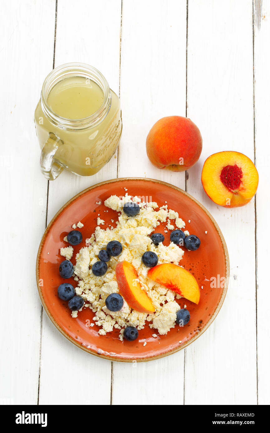 Still life with cottage cheese, smoothie, blueberry and peach on a white wooden background - Stock Image