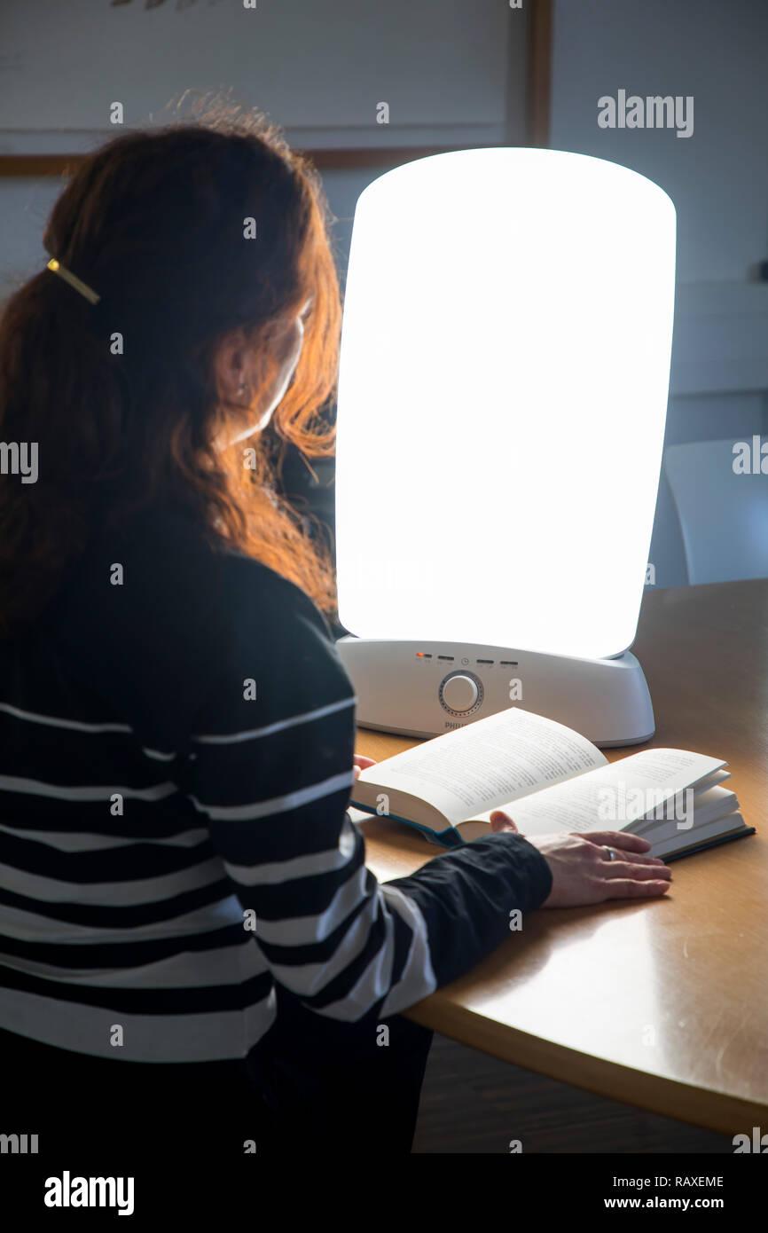 Lichttherapie mit Tageslichtleuchte, eine Frau sitzt vor einer Leuchte, die Tageslicht imitiert, Therapie gegen Winterdepression, wegen zu wenig Tages - Stock Image