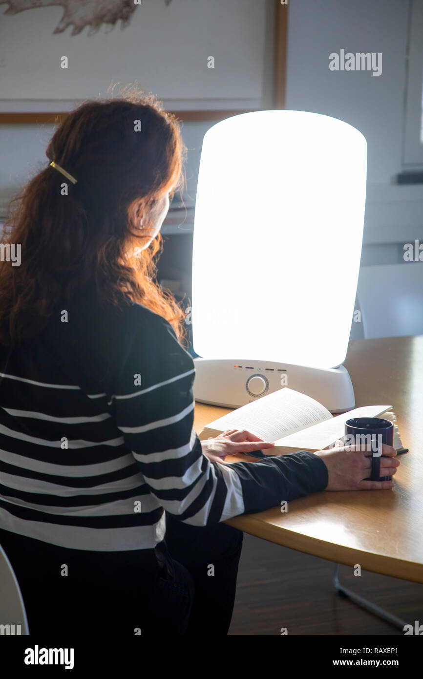 Light therapy with daylight lamp, a woman sitting in front of a lamp that imitates daylight, therapy against winter depression, because of too little  - Stock Image