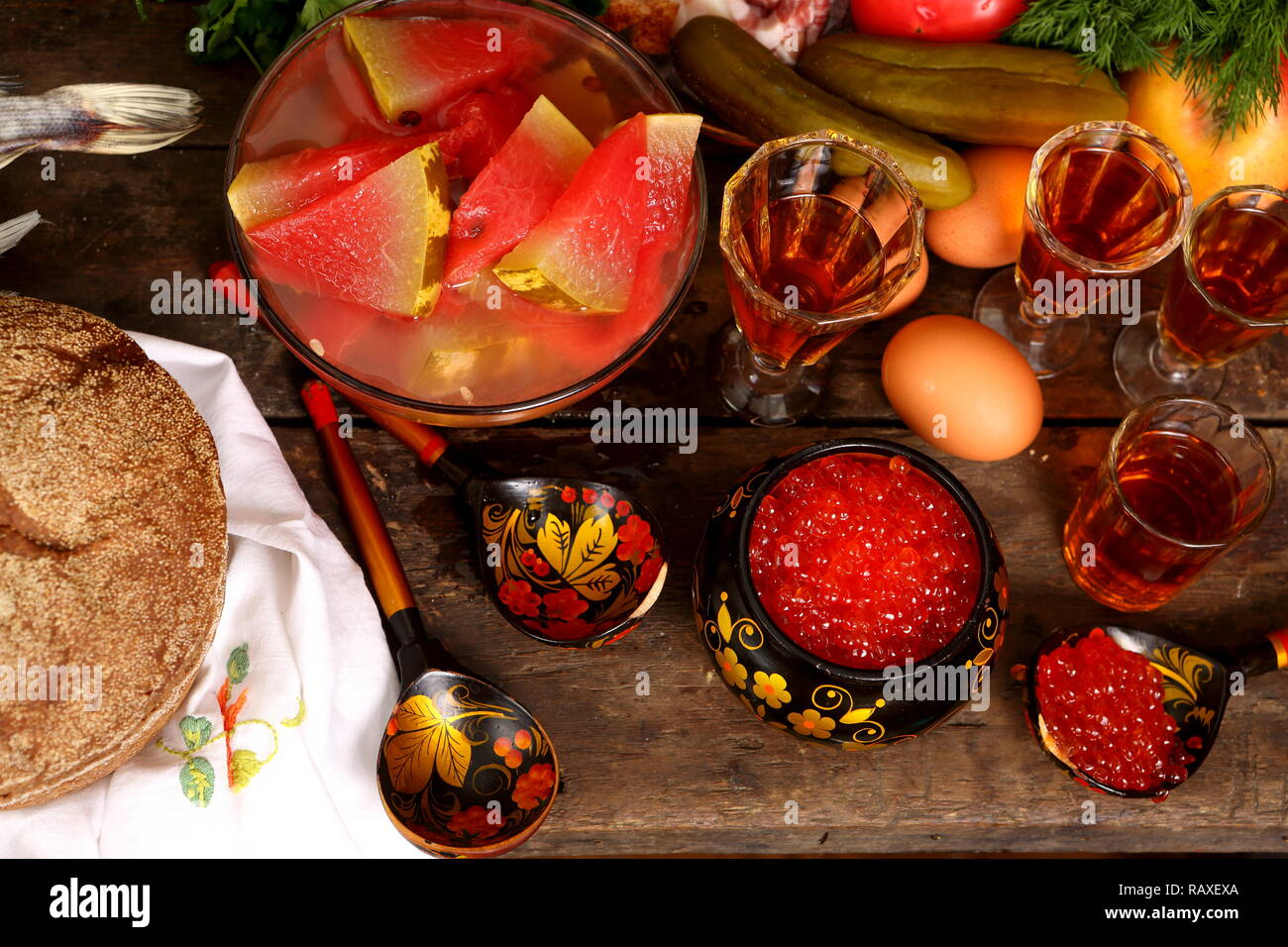 Still life with red caviar and vodka on a wooden table - Stock Image
