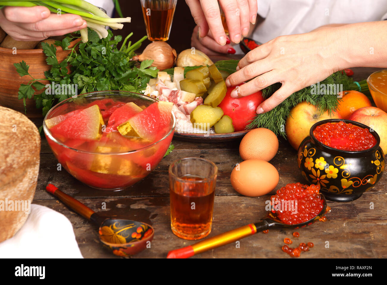 Female hands take food at the holiday table - Stock Image