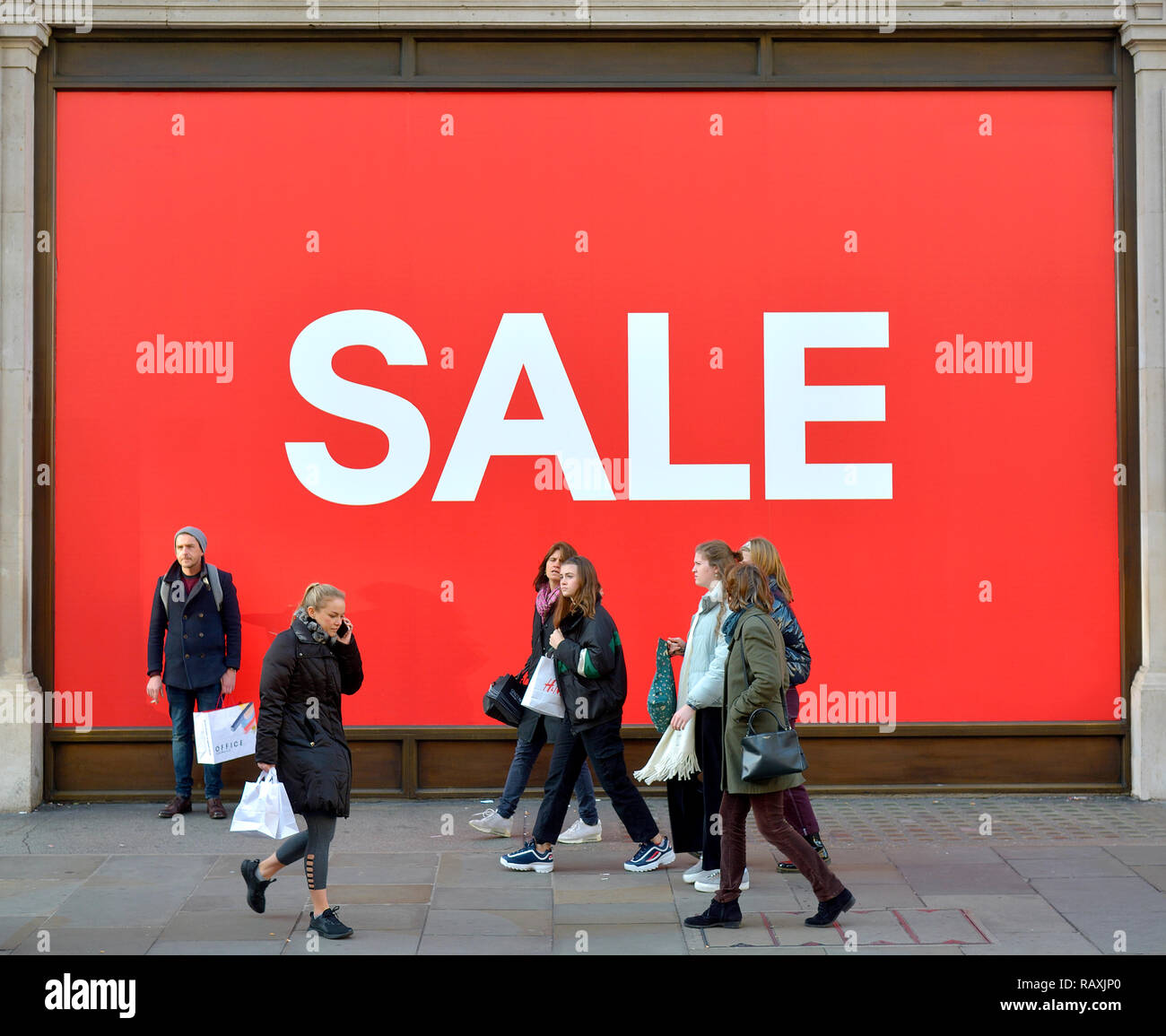 SALE sign in shop window (H&M, Regent Street) in January. London, England, UK. [SHOP LOGO DIGITALLY REMOVED] - Stock Image