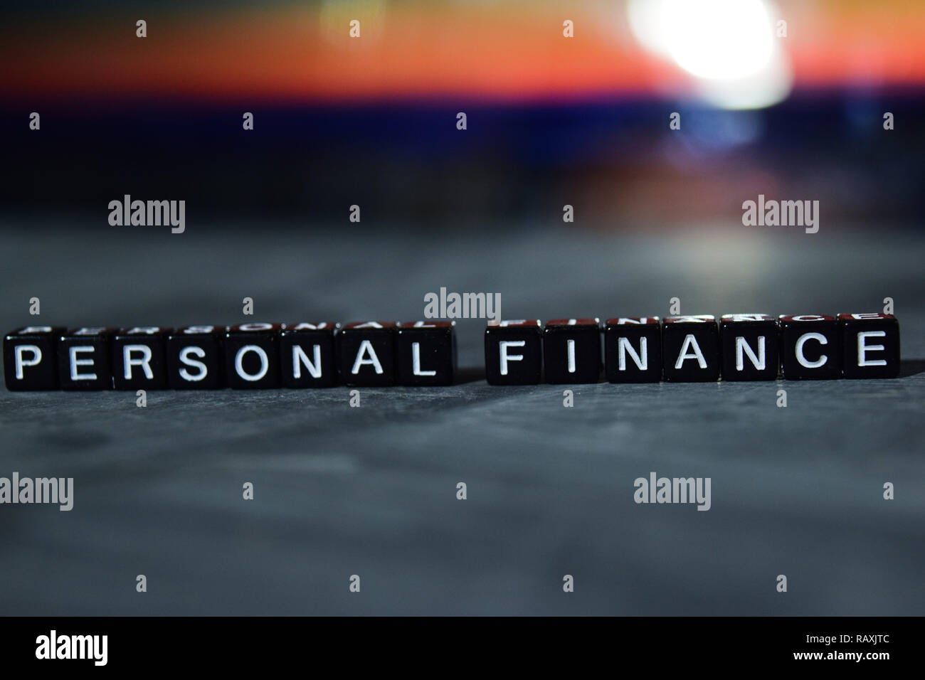 Personal finance on wooden blocks. Business and finance concept. Cross processed image with bokeh background - Stock Image