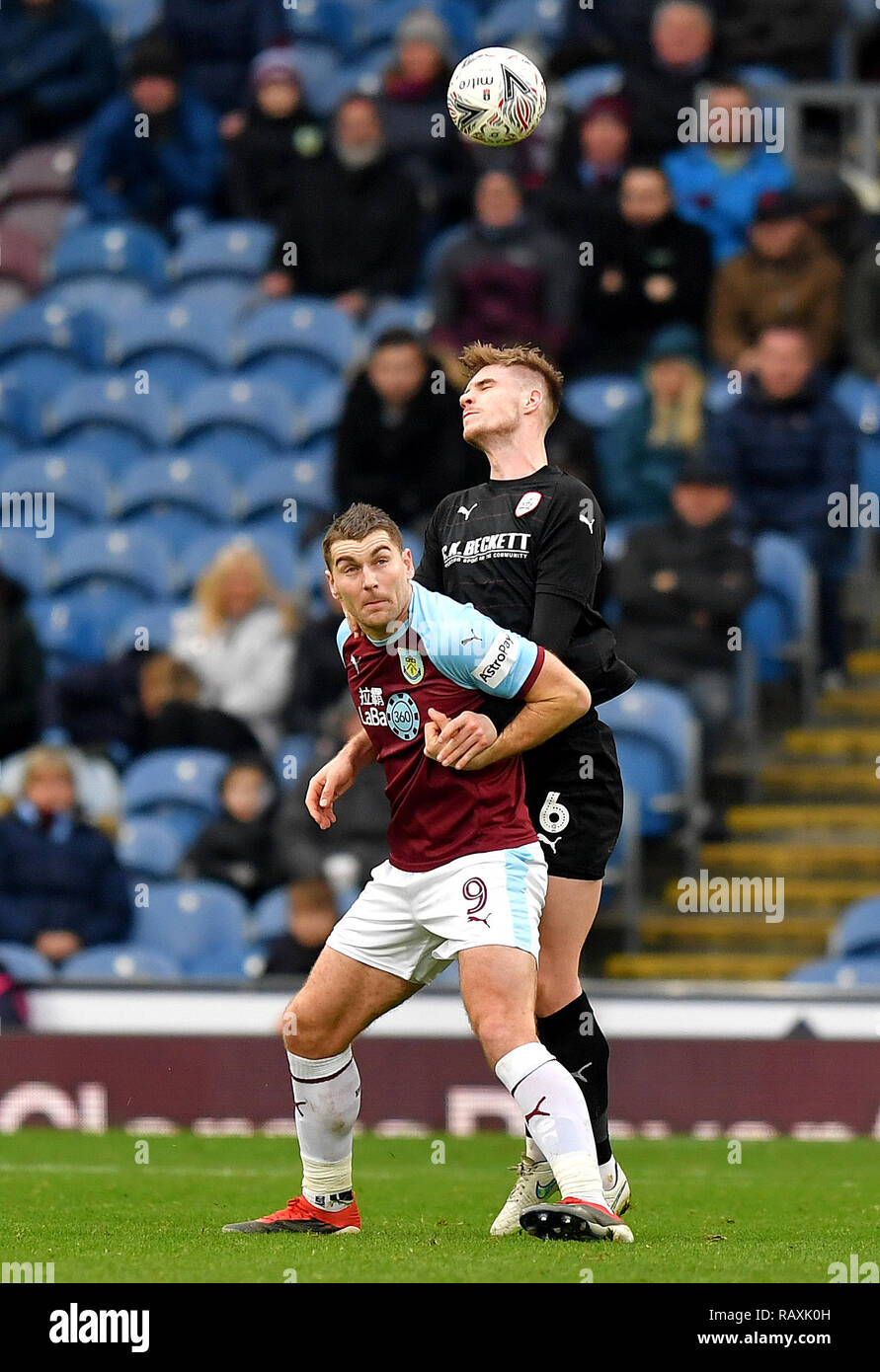Burnley's Sam Vokes (left) and Barnsley's Liam Lindsay (right) battle for the ball during the Emirates FA Cup, third round match at Turf Moor, Burnley. - Stock Image