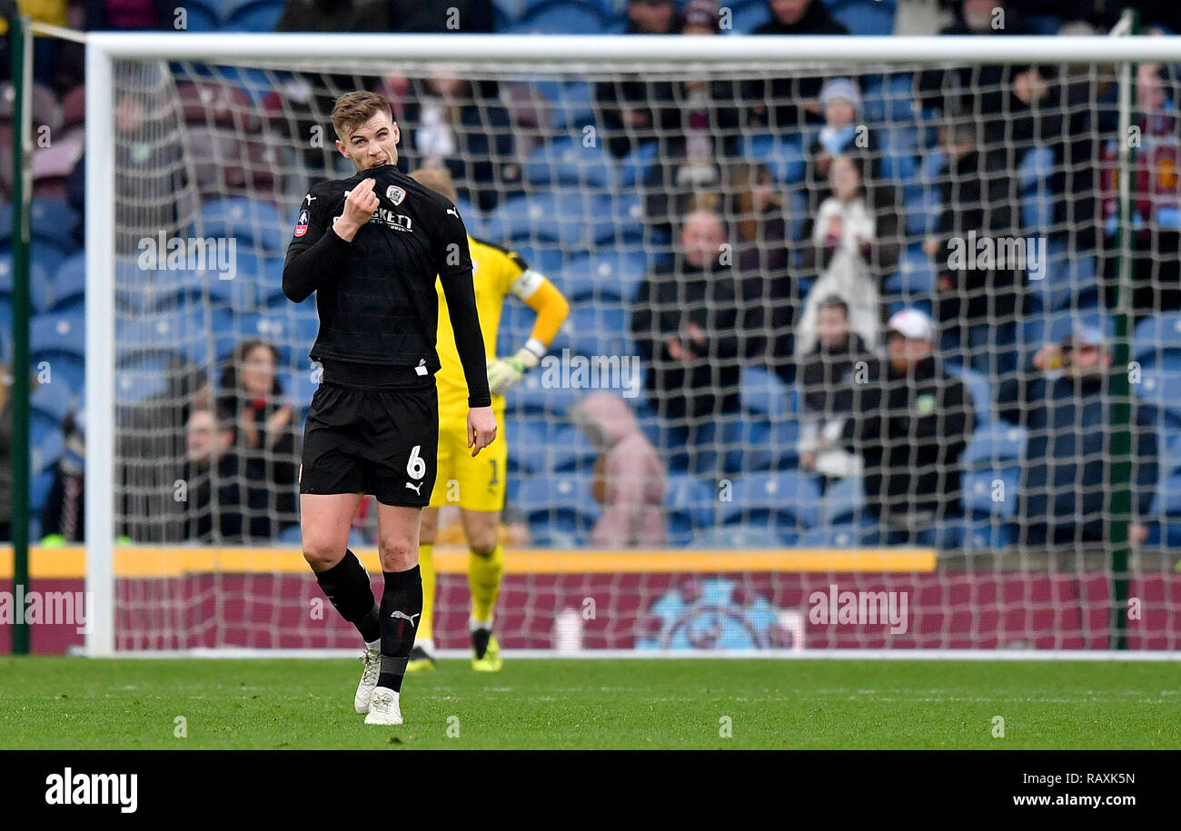 Barnsley's Liam Lindsay appears dejected after Burnley's Chris Wood scores his side's first goal of the game from the penalty spot during the Emirates FA Cup, third round match at Turf Moor, Burnley. - Stock Image