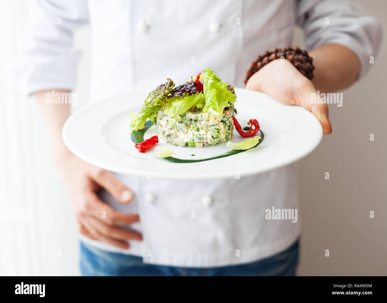 Chef holding Healthy Raw vegan salad in the white plate in restaurant - Stock Image
