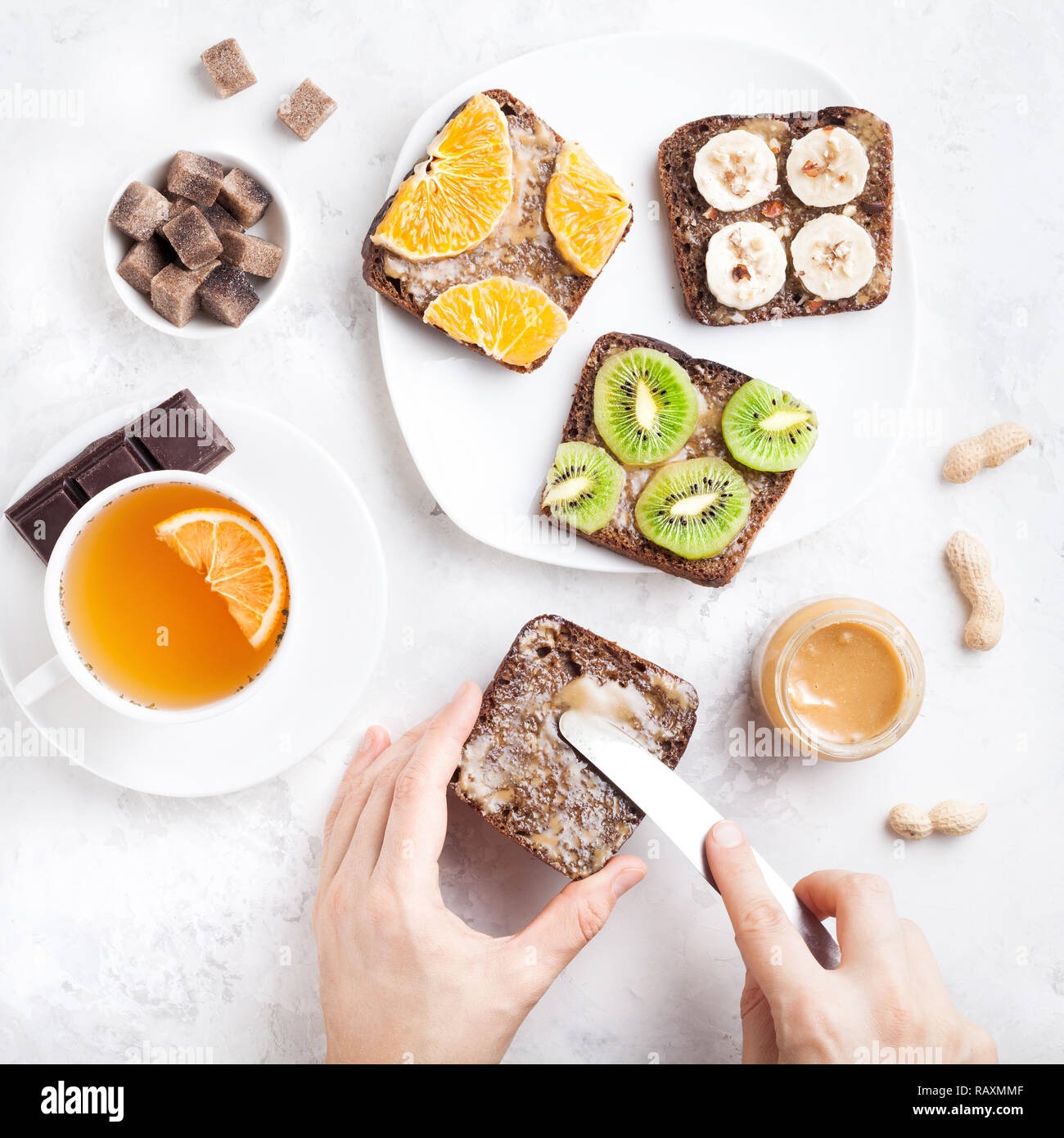 Woman hands spreading peanut butter on the bread in the morning on white marble background - Stock Image