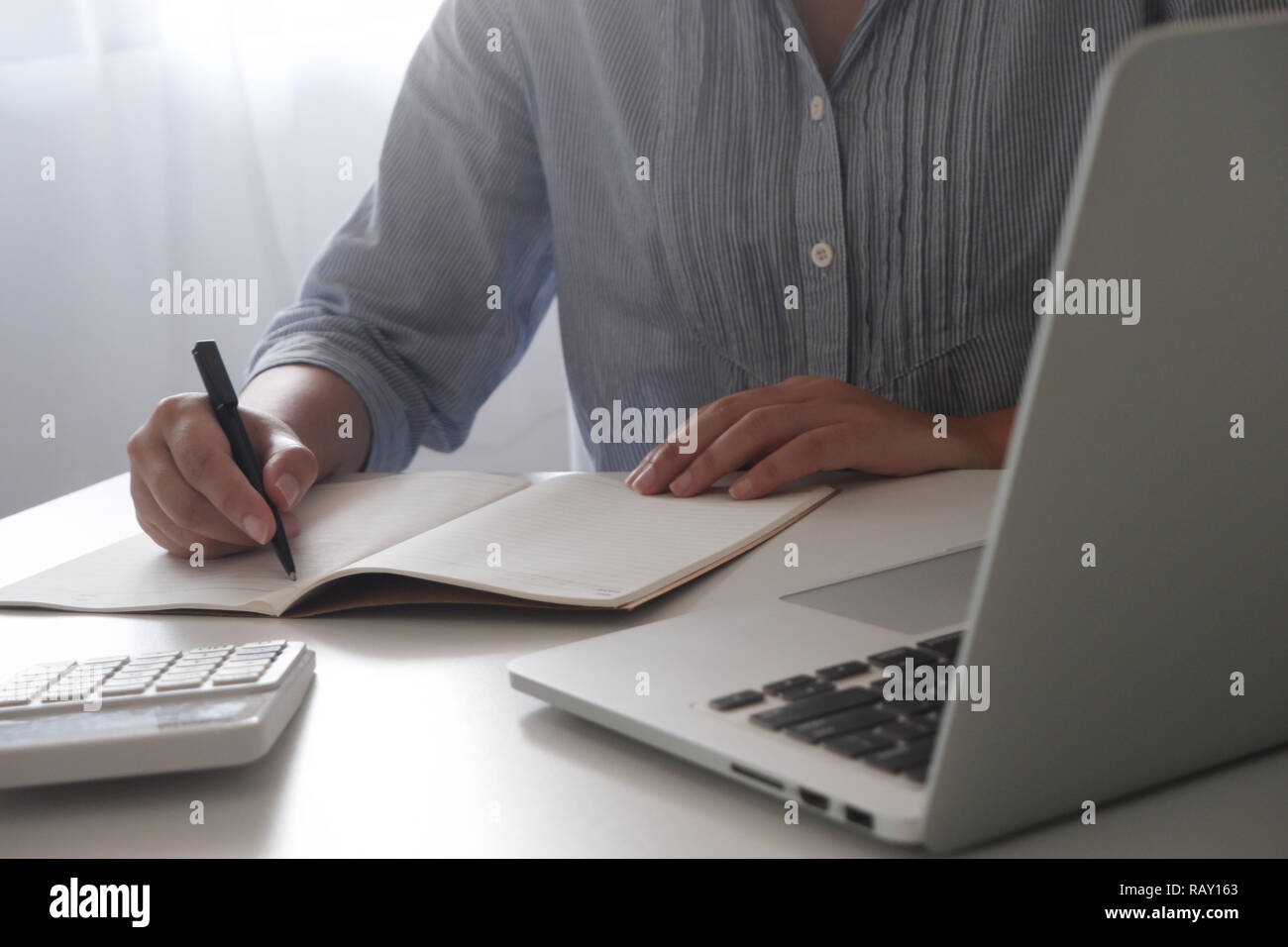 Cropped image of professional businesswoman working at her office via laptop  young female manager using portable computer device - Stock Image