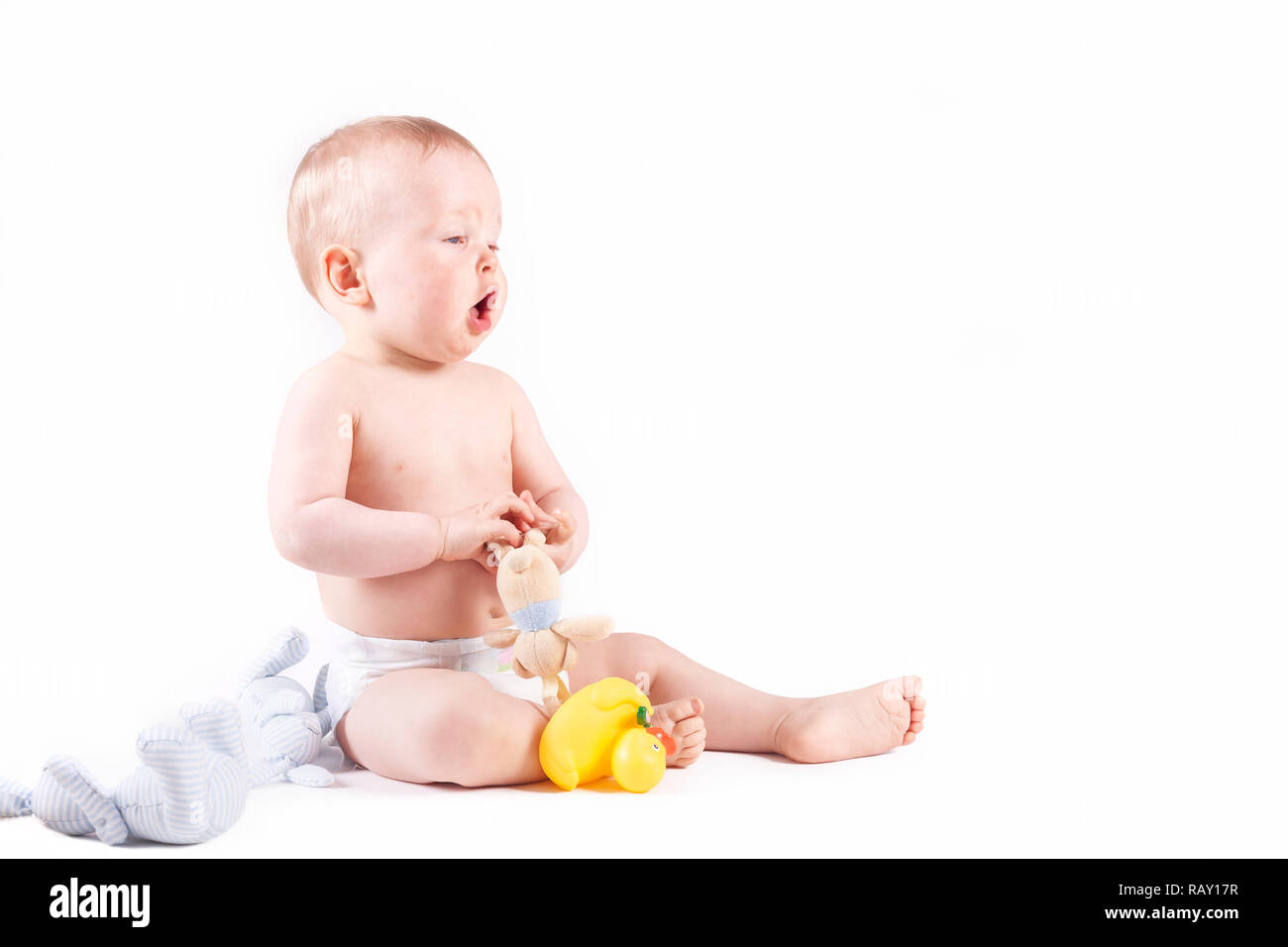Sneezing, Hiccuping 9 months old baby boy sitting on the ground with toys - studio shot - Stock Image