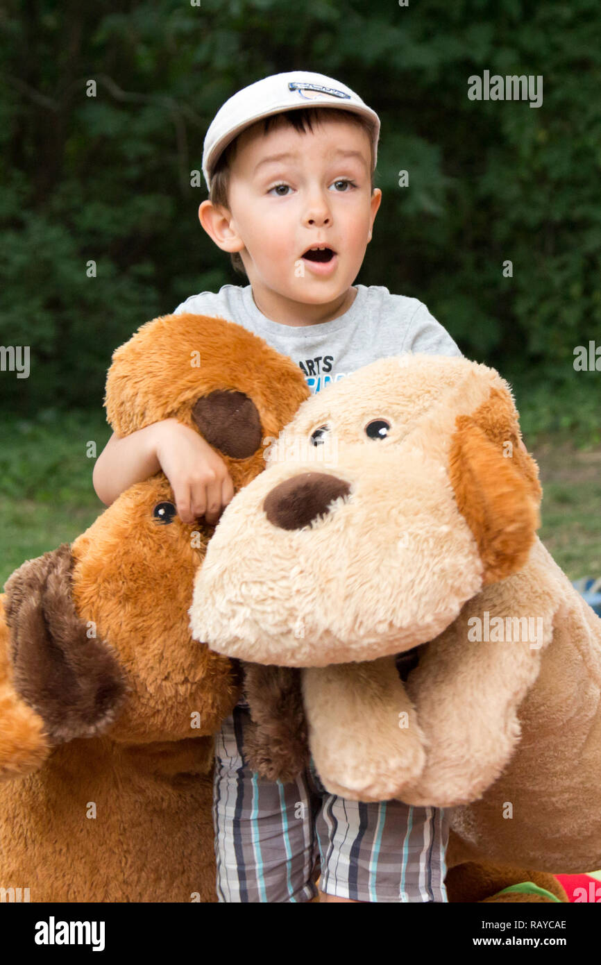 Boy child with big plush toy dogs expressing joyful surprise in a park - Stock Image