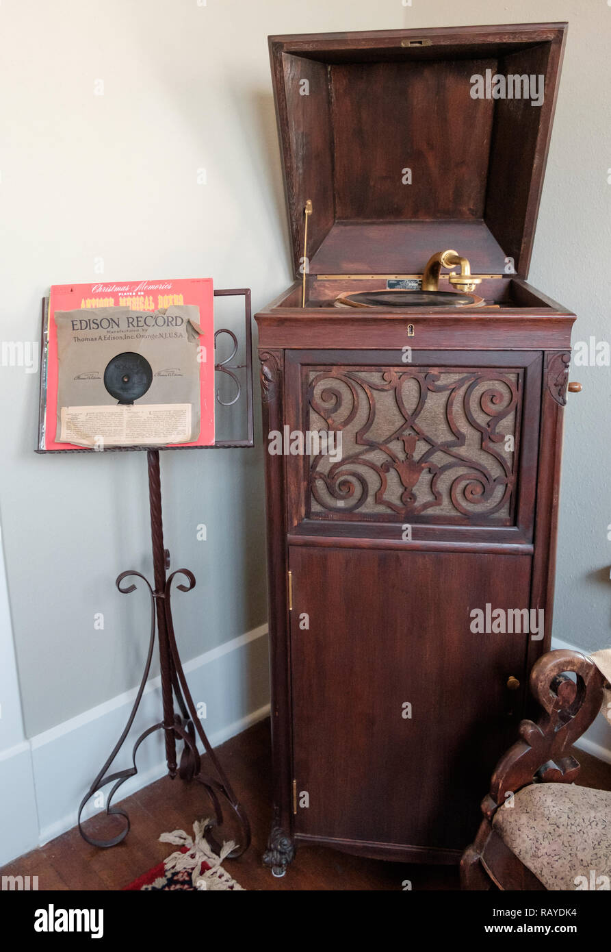 Antique record player in wooden cabinet with music stand & Edison record. Interior of Historic Texan Home, Chestnut Square Village, McKinney, Texas. - Stock Image