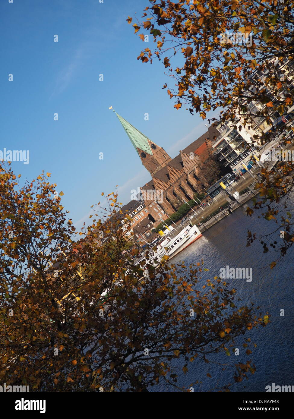 Bremen, Germany - River Weser with St. Martini church framed by trees in the foreground with slanted horizon - Stock Image