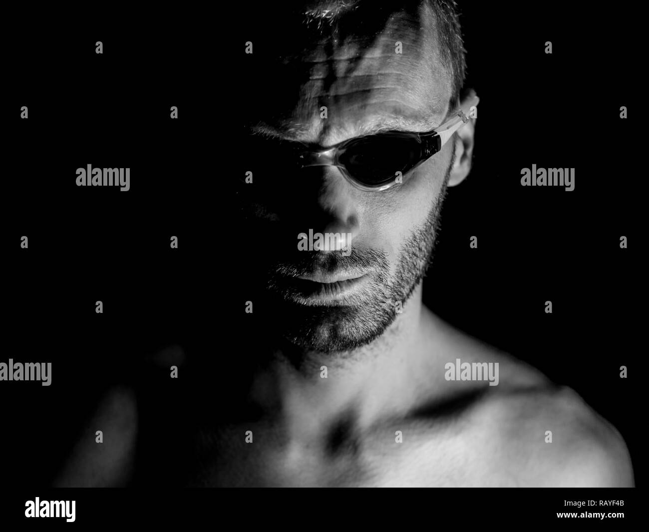 Portrait of unshaven adult caucasian man in swimming glasses. He looks straight to watcher. Black and white shot, low-key lighting. Isolated on black. - Stock Image