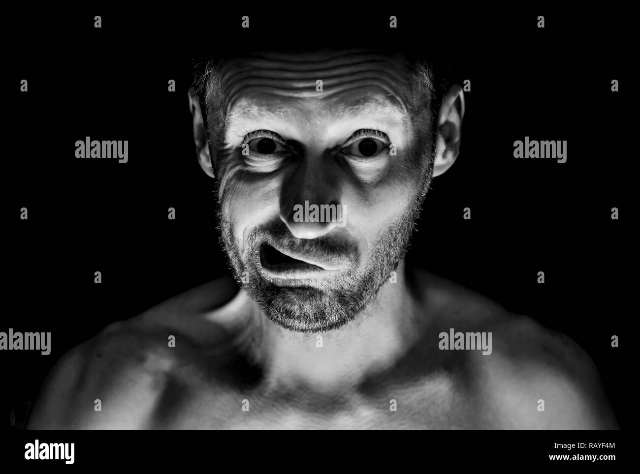 Portrait of unshaven adult caucasian man. He smiles like maniac and seems like madness. Black and white shot, low-key lighting. Isolated on black. - Stock Image