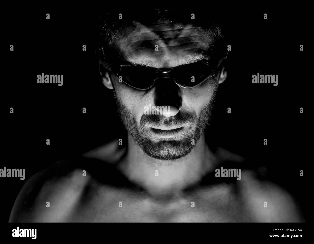 Portrait of unshaven adult caucasian man in swimming glasses. He smiles and looks straight to watcher. Black and white shot, low-key lighting. Isolate - Stock Image