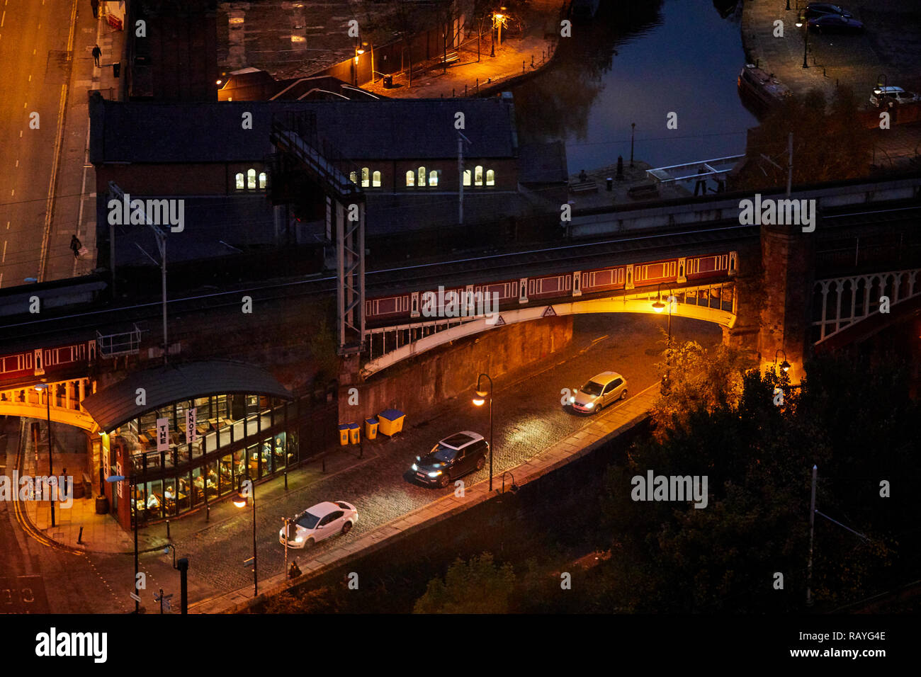Manchester at night Cattle Street in Castlefield and Deansgate railway station bridge, with The Knott pub in the railway arches - Stock Image