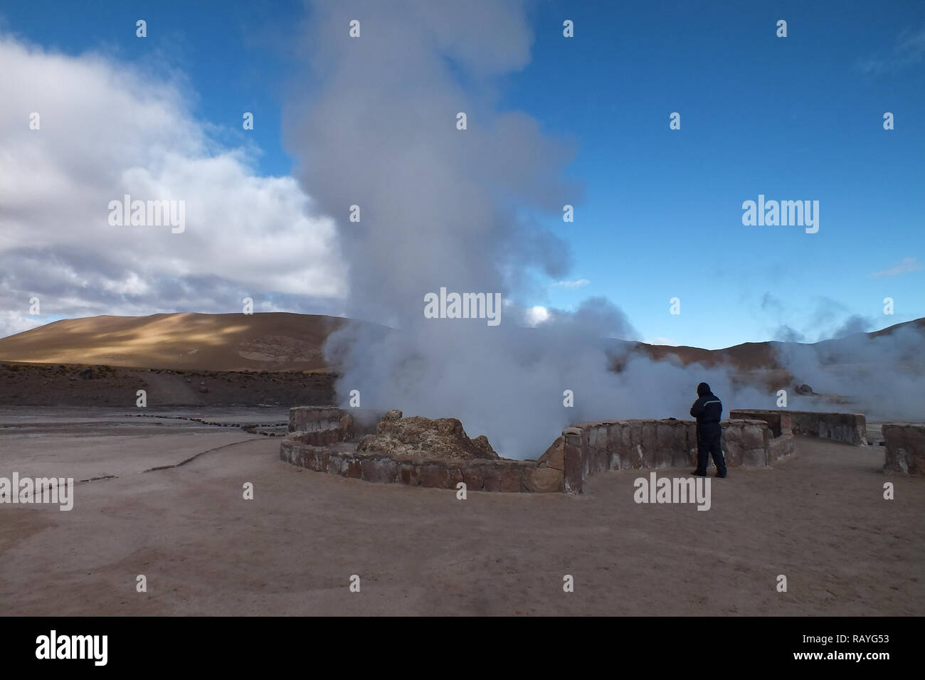 The largest geothermal of South America and the third of the world. Atacama desert-Chile. Tourists are trying to warm themselves up with hot steam. - Stock Image