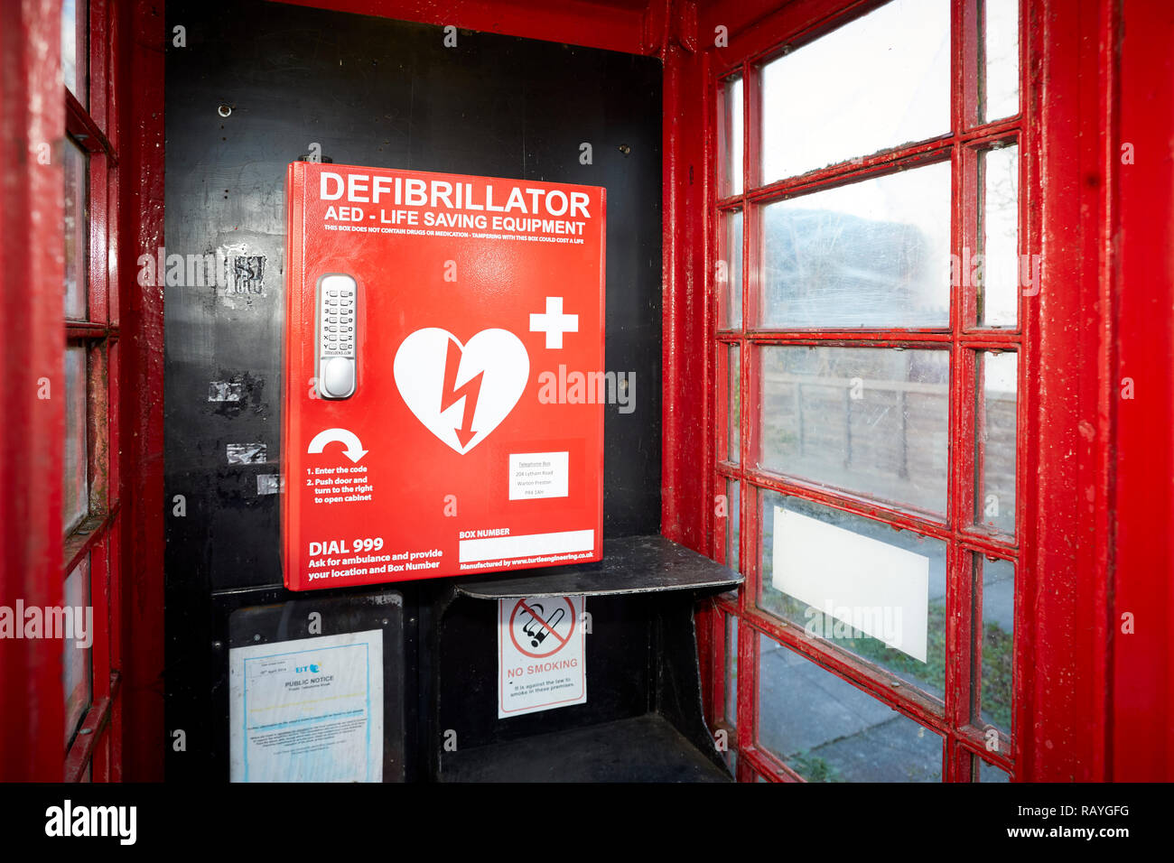 Emergency defibrillation automated external defibrillator (AED) located in an old red telephone box in a Lancashire Village - Stock Image