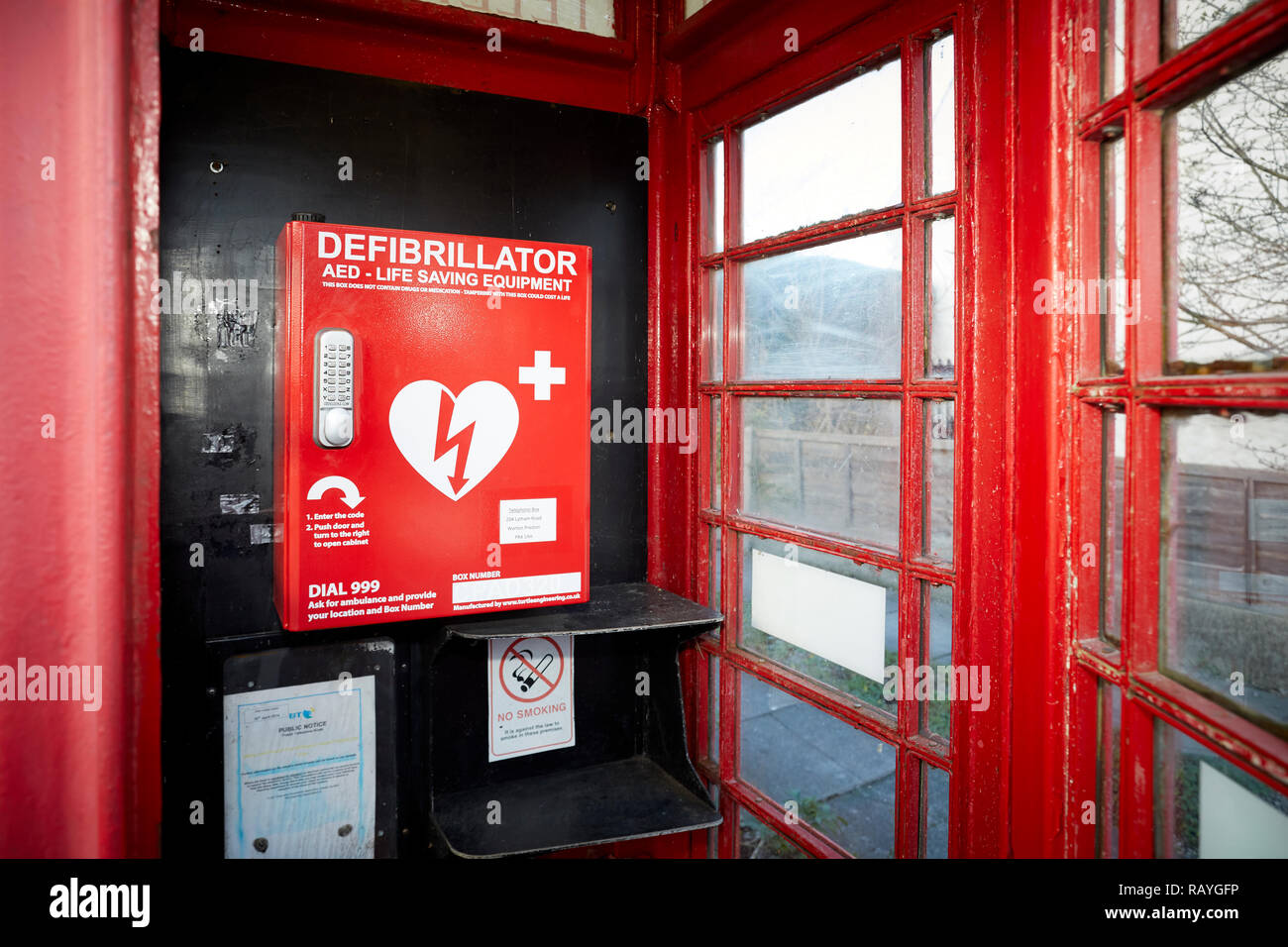 Emergency defibrillation automated external defibrillator (AED) located in an old red telephone box in a Lancashire Village Stock Photo