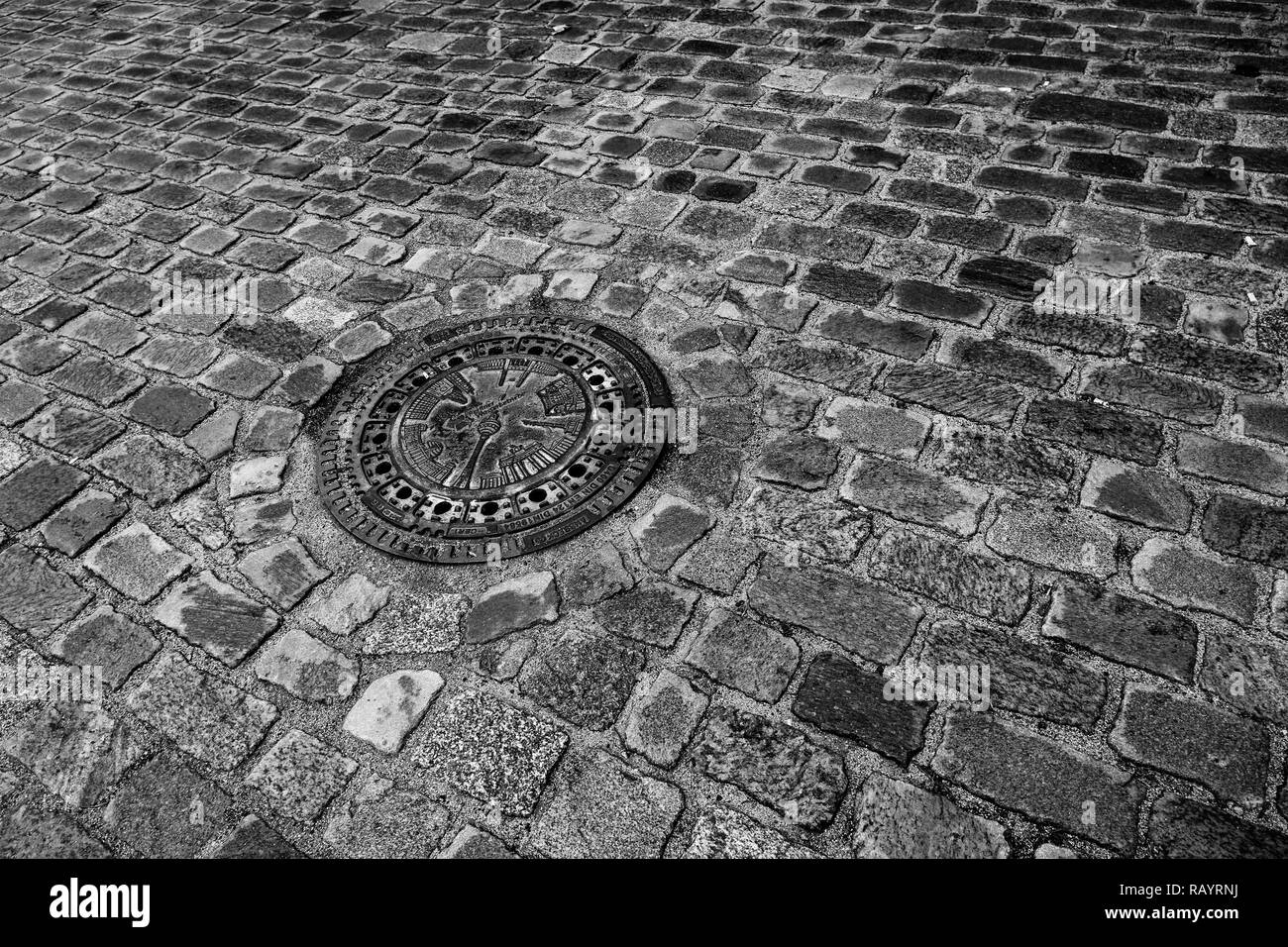 A cobblestone street In Berlin, Germany with the television tower on a manhole cover (black and white) - Stock Image