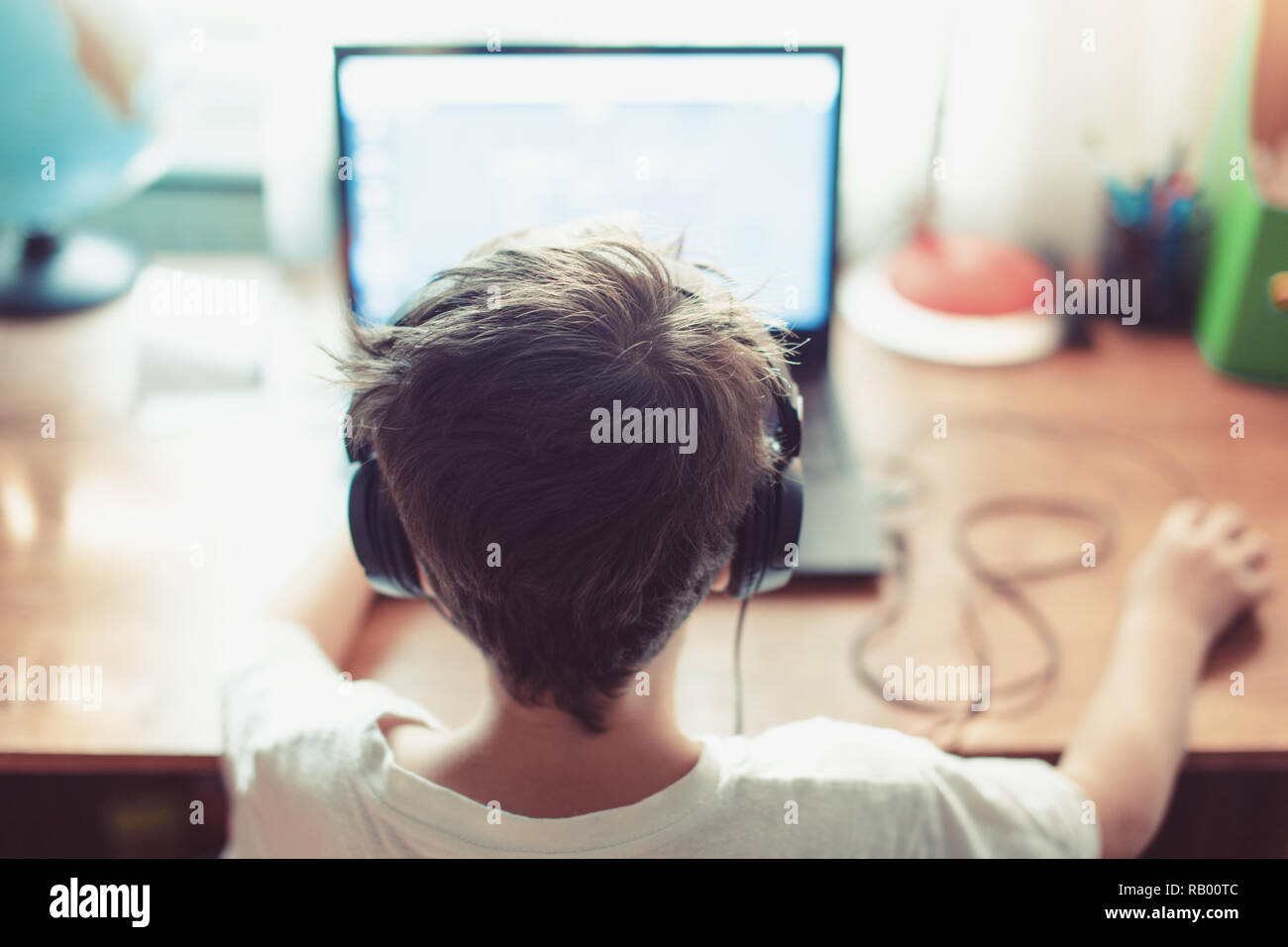 Little dependent gamer kid playing on laptop indoors - Stock Image