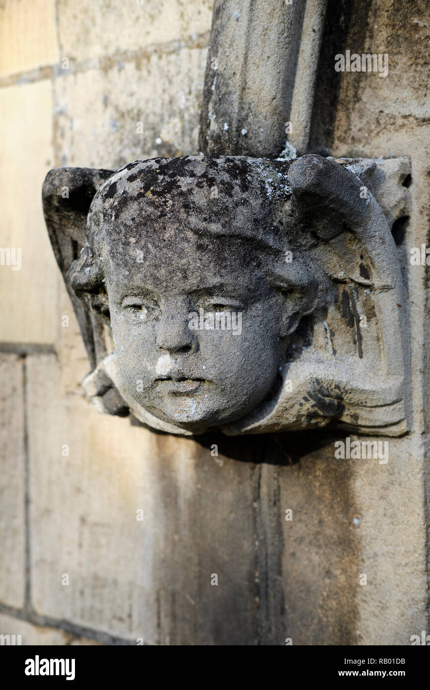 Ecclesiastical sculpture of an angelic face caved in stone decorating the entrance to a church, Eaton Socon, UK. Stock Photo