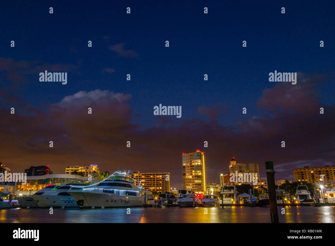 Illuminated cityscape with boats at blue hour - Stock Image