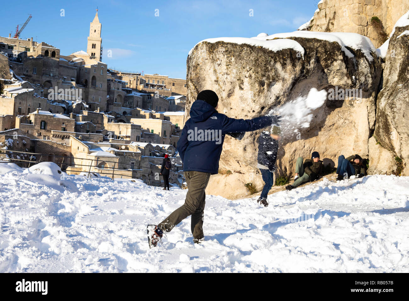 Matera, MT, Italy. 4th Jan, 2019. Children seen playing with snowballs, while tourists are sunbathing among the i Sassi di Matera after a long snowfall when the sun shines on the snow-covered rocks of matera, making a beautiful postcard of the European capital of culture 2019. Credit: Cosimo Martemucci/SOPA Images/ZUMA Wire/Alamy Live News Credit: ZUMA Press, Inc./Alamy Live News - Stock Image