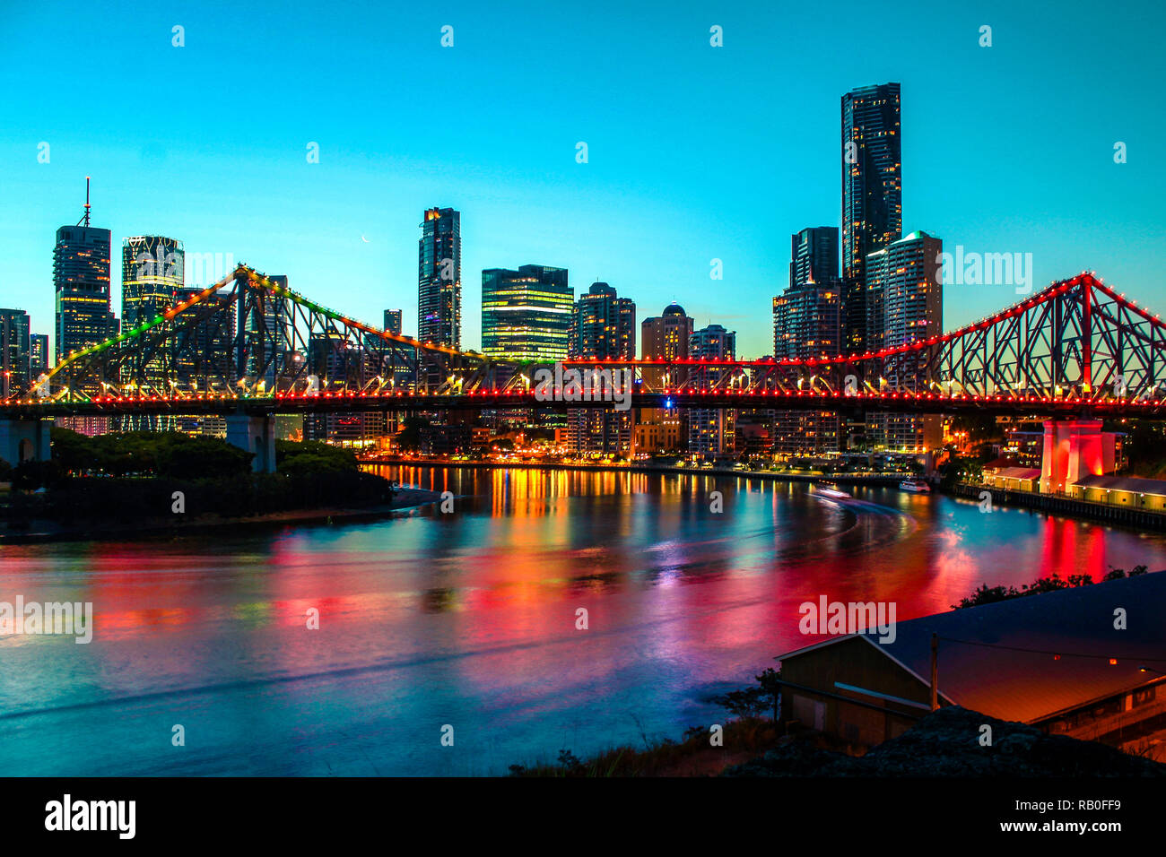 Colourful skyline of Brisbane by night with illuminated Story Bridge and clear blue sky (Brisbane, Queensland, Australia) - Stock Image