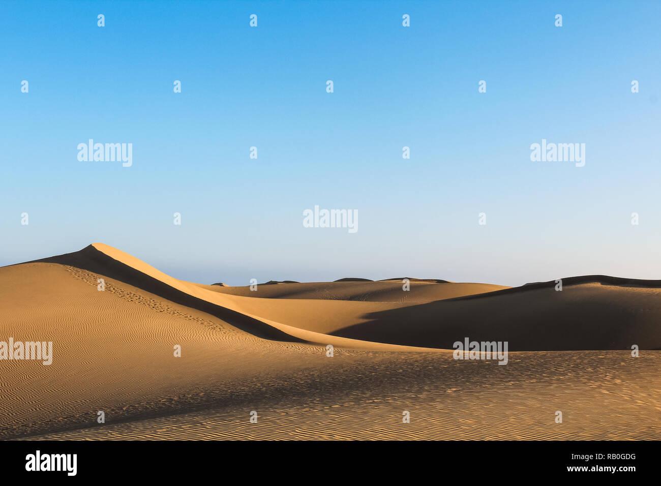 Cascading sand dunes in the vast desert casting long shadows during sunset (Dunas de Maspalomas, Gran Canaria, Spain, Europe) - Stock Image