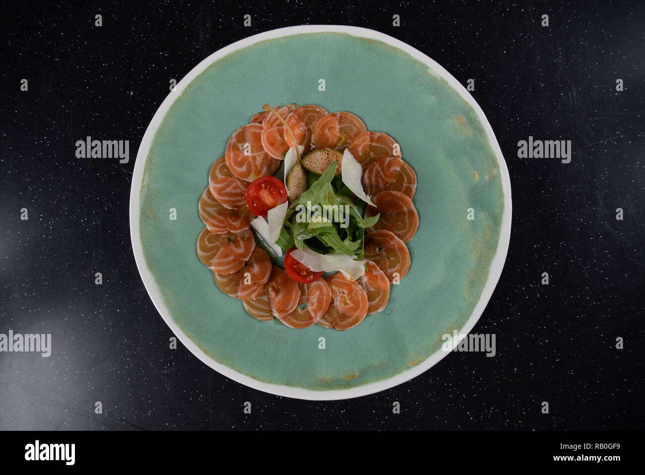 Luxury restaurant lachs red salmon appetizer with cheese on round dish, flat lay view from above - Stock Image