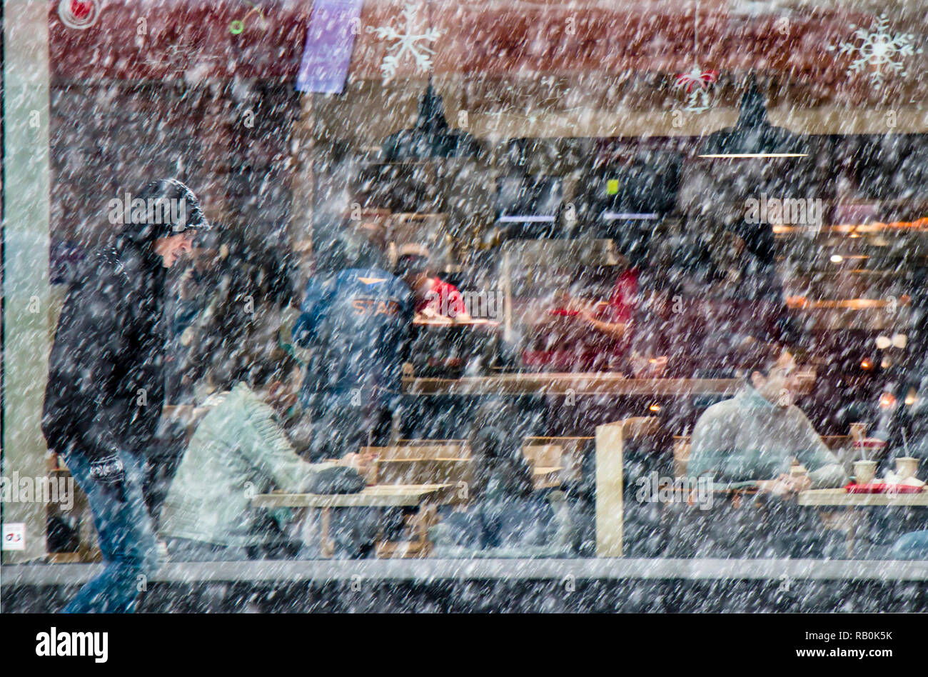 Belgrade, Serbia - December 15, 2018: Blurry man walking alone city street in heavy snowfall and people sitting in a restaurant window behind him Stock Photo